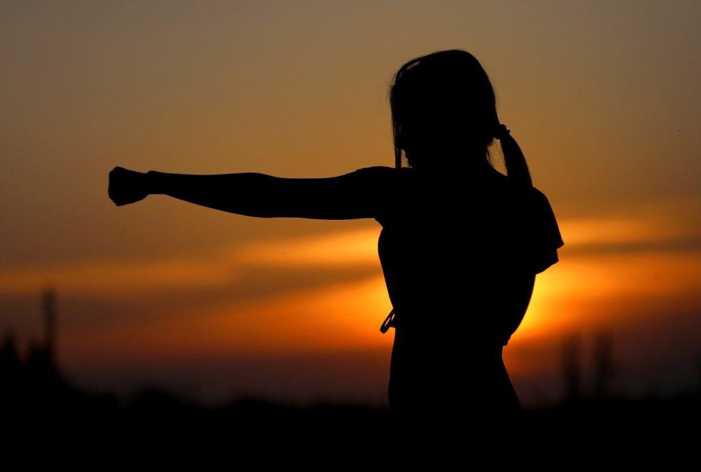夕日を背景に空手の突きの女性