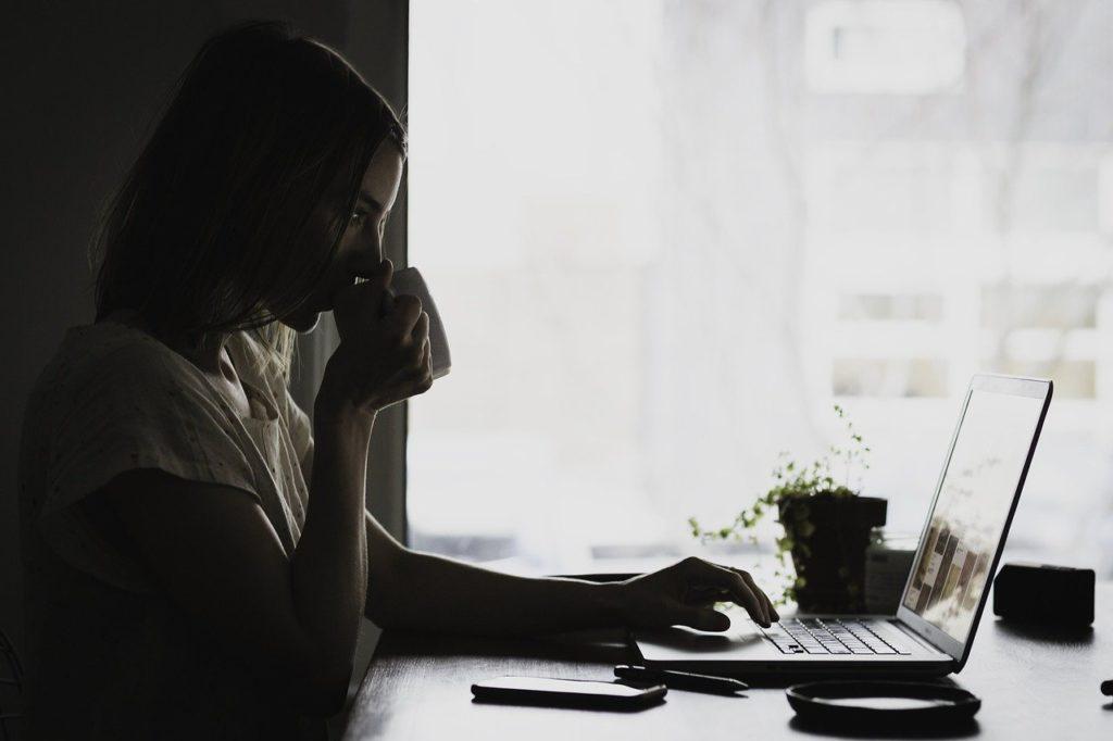 女性が暗い様子でパソコンを操作している