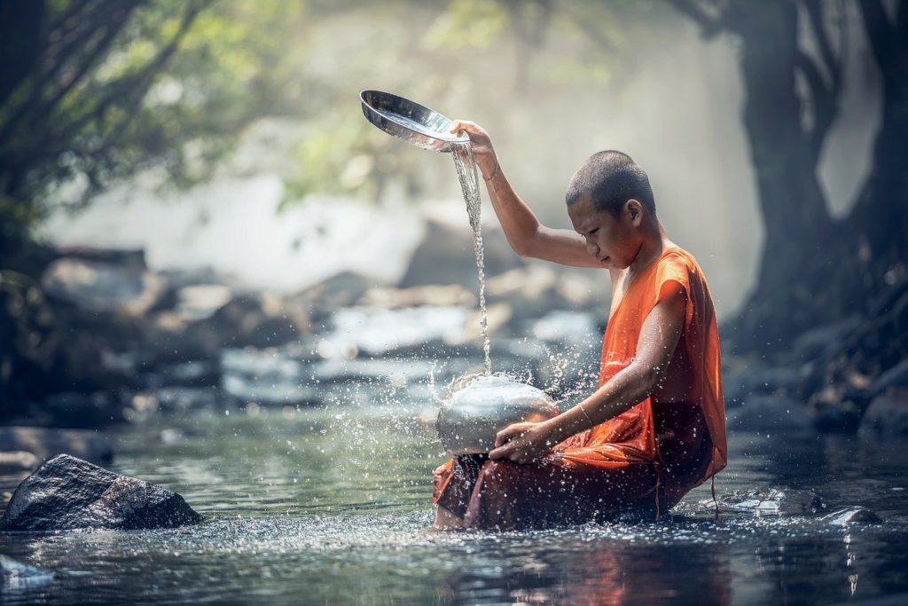 少年が川で水をくんでいる