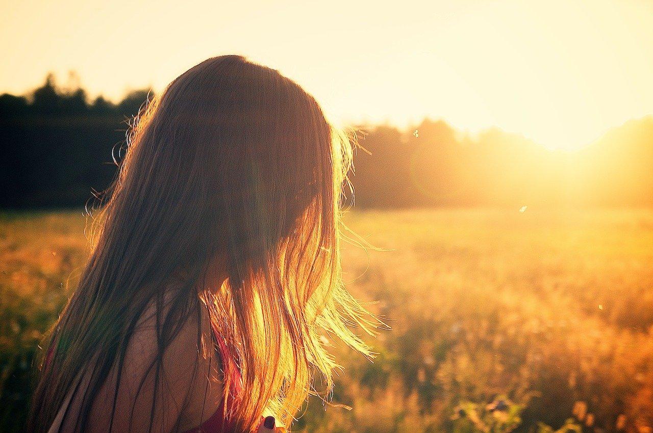 遠くの夕日を悲しそうに眺める女性