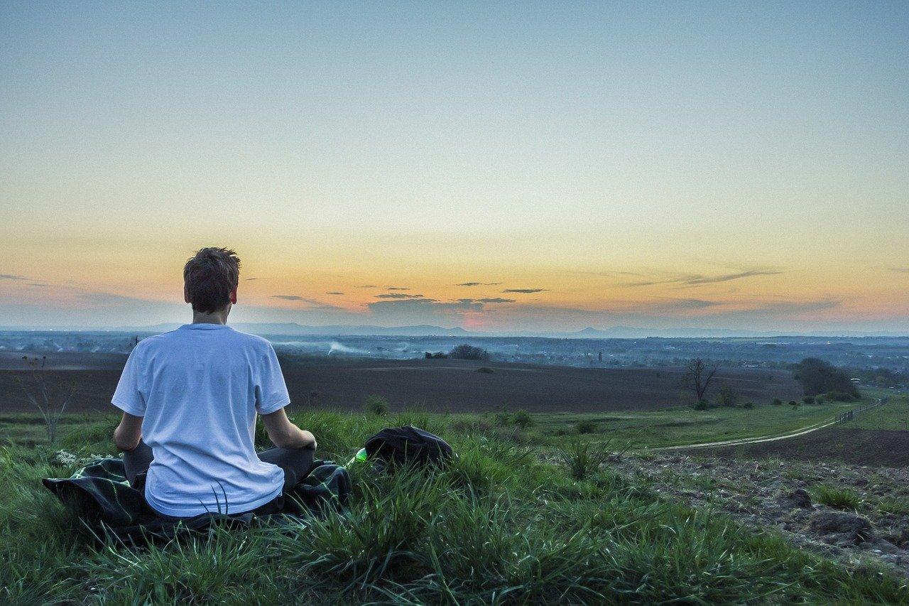 男性が夕焼けをみて瞑想している